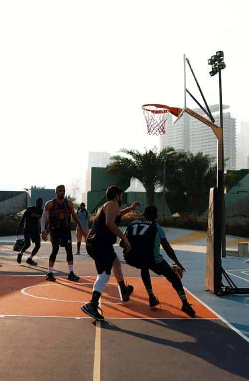 Tall basketball players playing outdoor basketball on court, Player is driving baseline while the defender is trying to steal the ball.