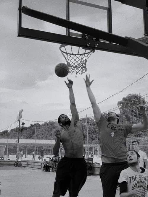 Two tall basketball players jump up for a rebound in black and white photo.