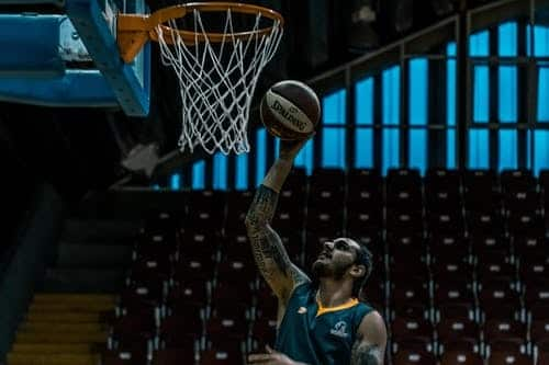 Tall professional basketball player standing underneat the hoop shotting the ball into the hoop.