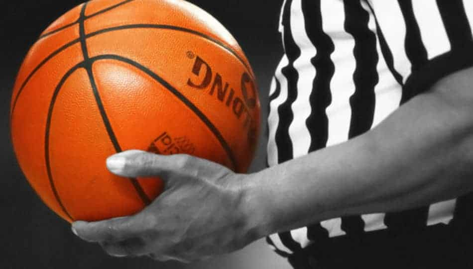 Black and white image with a referee holding and orange ball.