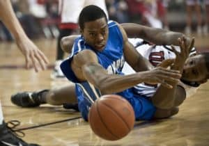 Two players during a game dive for a loose ball.
