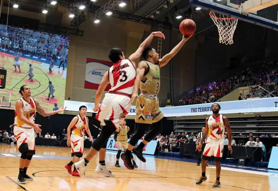 Player laying up the basketball into the basket while getting fouled.
