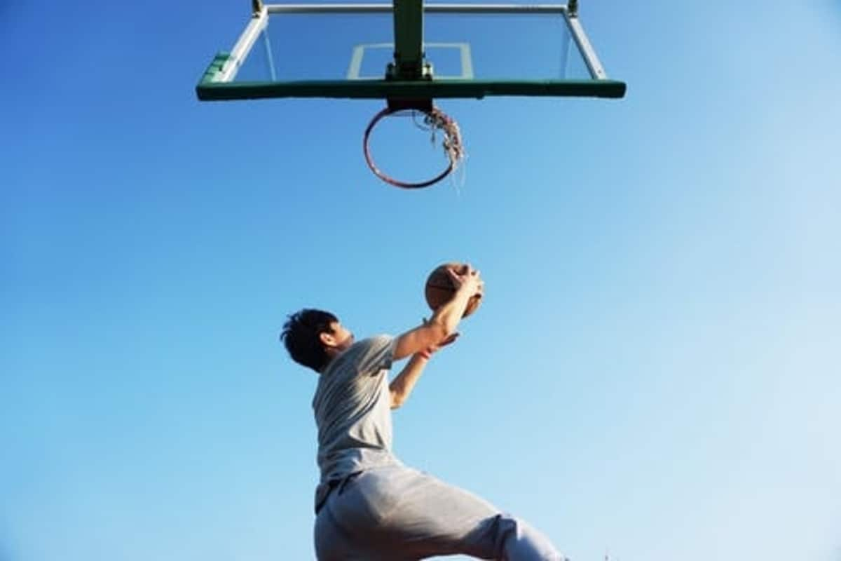 basketball player doing a layup on outdoor up sky showing